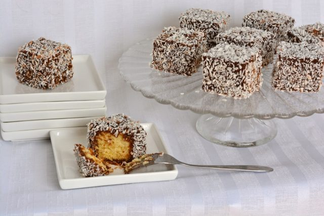 A tray of gluten free lamingtons with one cut and ready to bite into.