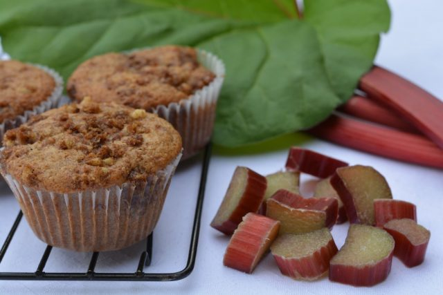 A baking rack with gluten free rhubarb streusel muffins surrounded by chopped rhubarb and a rhubarb leaf