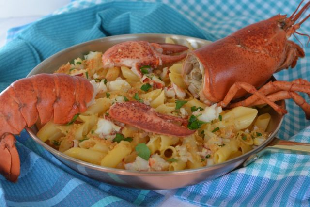 A dish of gluten free Lobster Macaroni and Cheese decorated with the head and tail.