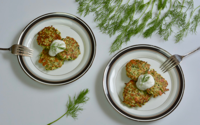 Two plates serving up Pan Fried Zucchini Fritters topped with sour cream and garnished with dill.