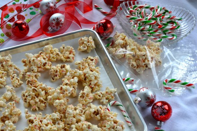 A pan with clumps of White Chocolate Candy Cane Popcorn beside the gift bags, candy canes and ribbon ready for gift wrapping.