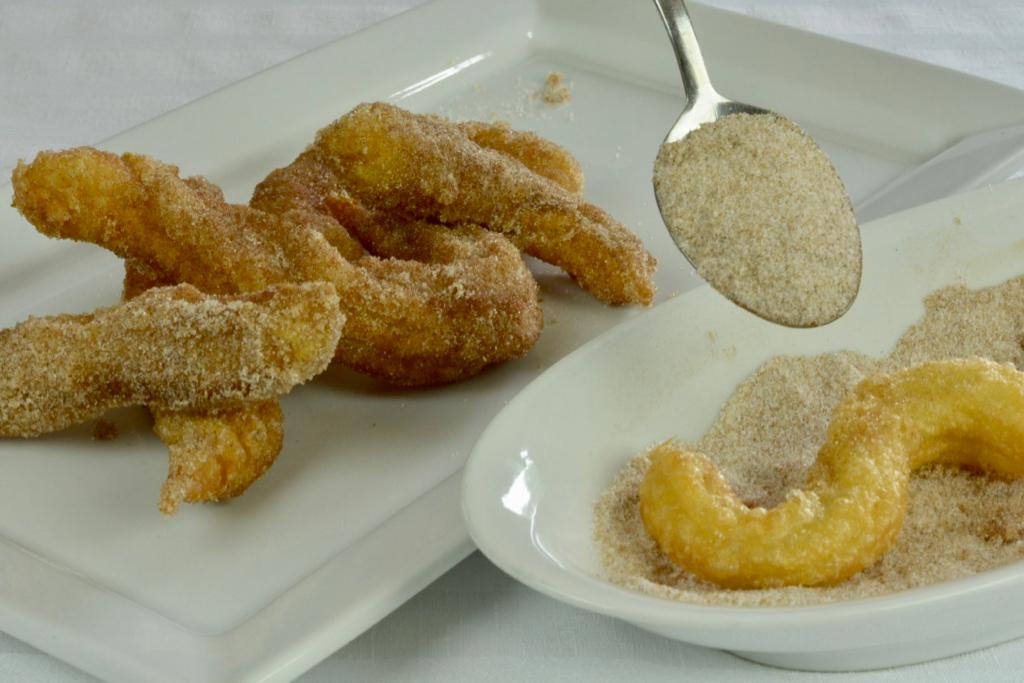 Sprinkling cinnamon-sugar on freshly deep-fried churros.