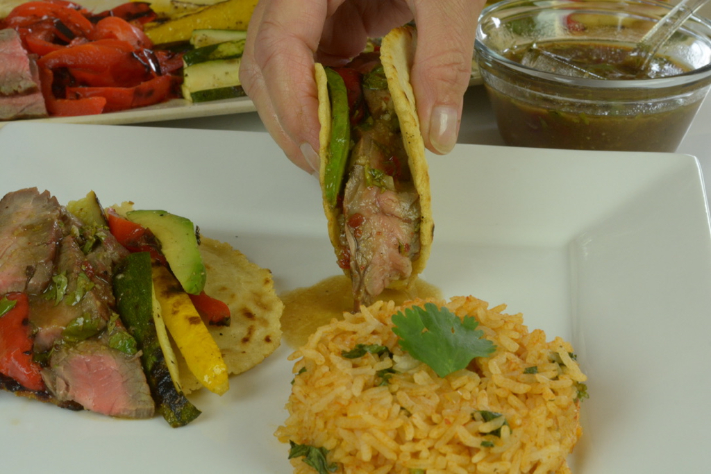 Flank Steak in corn tortillas with grilled vegetables and Mexican rice.