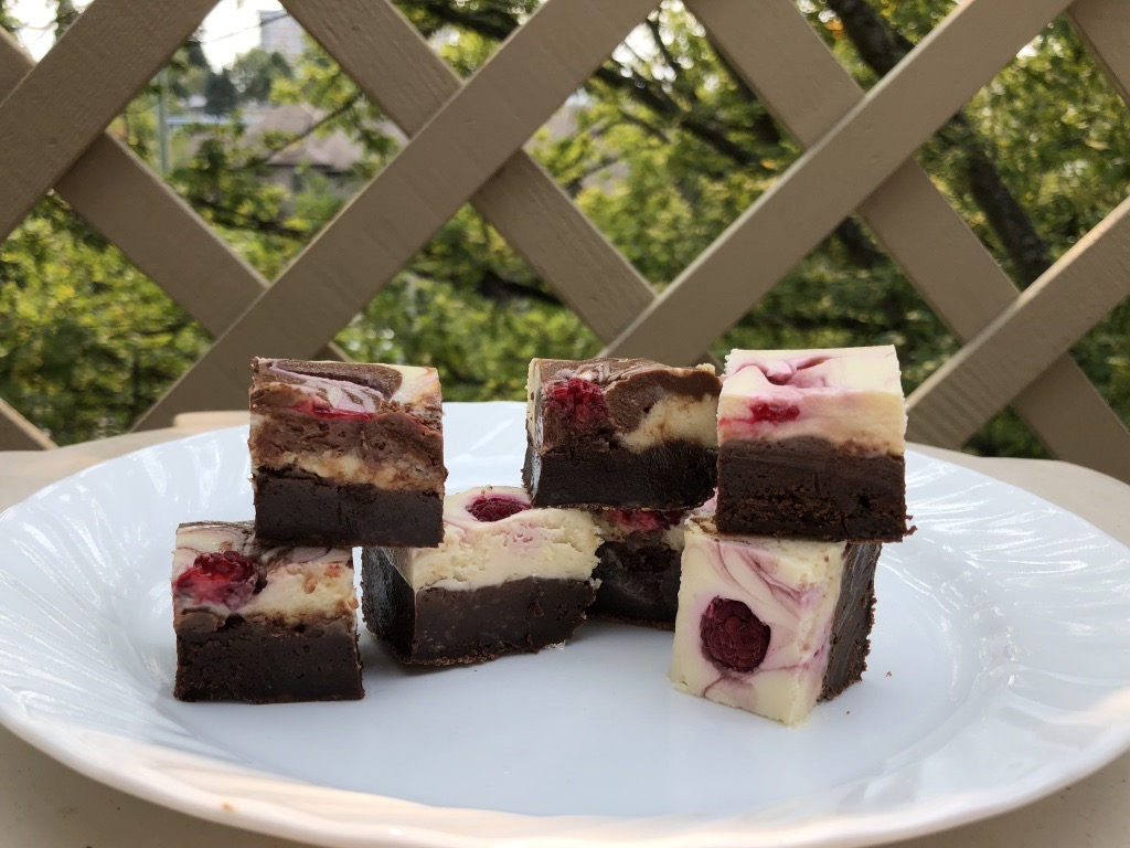 Raspberry Swirl Cheesecake Brownies cut on a plate and ready to eat.