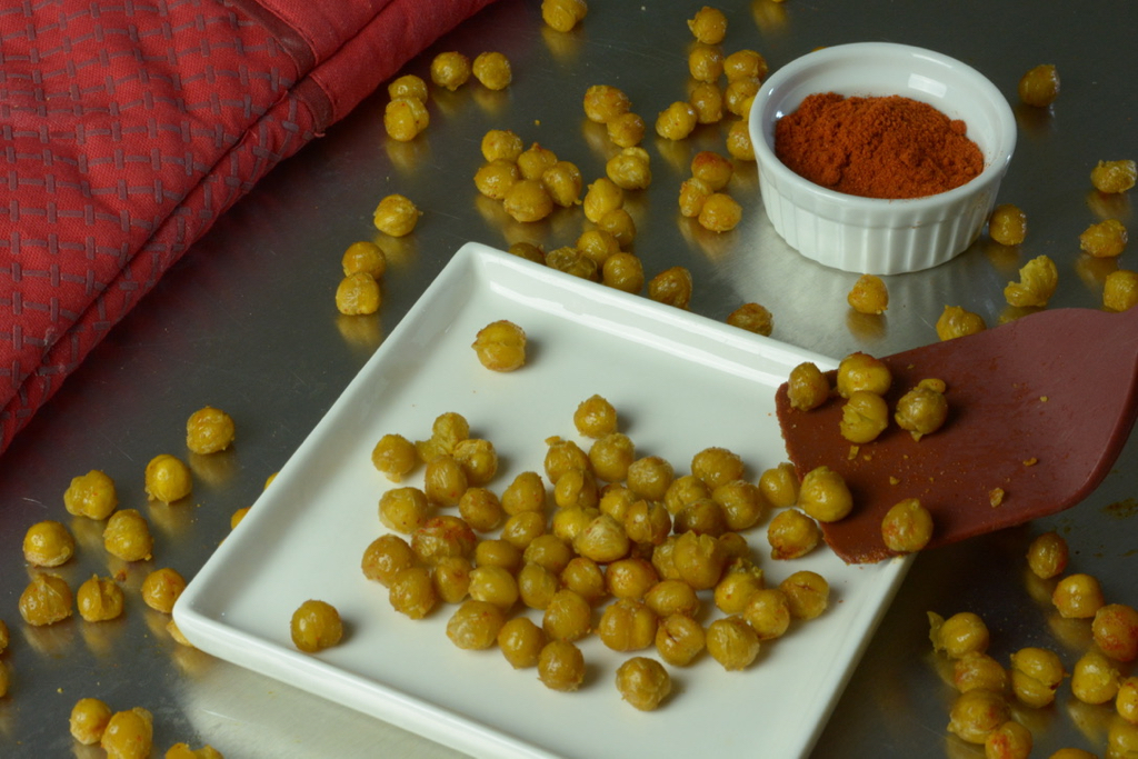Roasted Chickpeas on a plate with a dish of paprika.