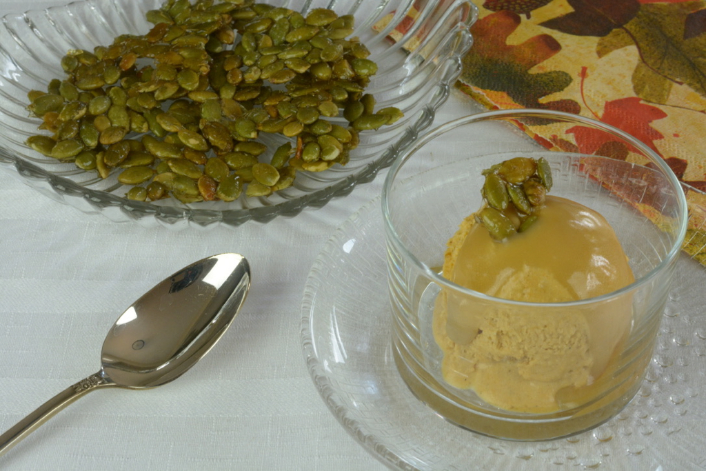 Homemade Pumpkin Ice Cream with Bourbon Caramel Sauce topped with sweet and salty candied pumpkin seeds.